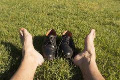 Feet relaxing in the grass. With his shoes royalty free stock photography