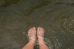 Feet relaxing in the river Stock Photos