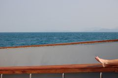 Feet relaxing on a sailboat with ocean background Royalty Free Stock Images