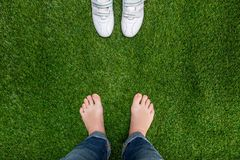 Feet resting on grass with sneakers standing opposit Royalty Free Stock Photography