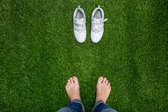 Feet resting on grass with sneakers standing opposit Royalty Free Stock Photos