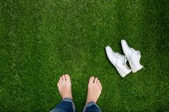 Feet resting on green grass with lying sneakers Stock Photos