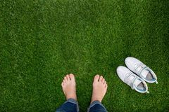 Feet resting on green grass with sneakers Royalty Free Stock Photography