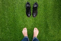 Feet resting on green grass with standing opposite boots Royalty Free Stock Images