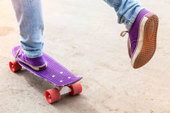 Feet of riding skateboarder in jeans and gumshoes Royalty Free Stock Photography