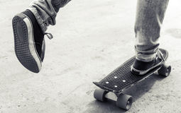 Feet of riding skateboarder in jeans and gumshoes Stock Images
