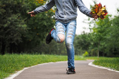 Feet on the road. Ripped jeans, a dance, a bouquet of autumn leaves Royalty Free Stock Images