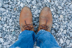Feet on rocky ground. Take one yourself wearing brown leather boots Stock Photos