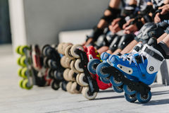 Feet of rollerbladers wearing inline roller skates sitting in outdoor skate park, Close up view of wheels befor skating. Feet of rollerbladers wearing inline royalty free stock photos
