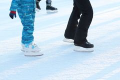Feet rolling on skates man on the ice rink stock image