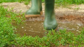 Feet in rubber boots fun to jump across the puddle. Feet in rubber boots go into a puddle. begins to trample and jump in a puddle. Splashes fly in all directions stock video footage