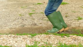 Feet in rubber boots jumping on a puddle. Children`s feet in rubber boots go into a puddle. The child begins to raise his legs high, creating large sprays. The stock video footage