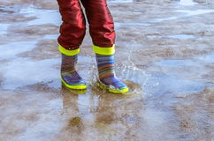 Feet in rubber boots Stock Photos