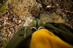 Feet in rubber boots standing in the shallow river Stock Photos