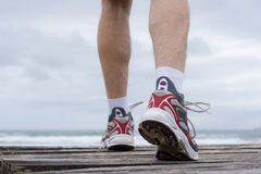 Feet of runner on a beach. Details of feet of runner in front of a beach Stock Photo