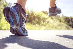 Feet of runner running or jogging on a road in summer stock photography