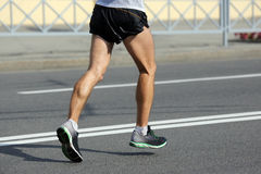 Feet running athlete at the distance of a marathon Royalty Free Stock Images