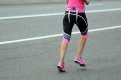 Feet running athlete woman at the distance of a marathon Stock Photos