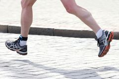 Feet running distance athlete on the stone pavement. The feet running distance athlete on the stone pavement Stock Photo