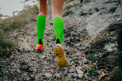 Feet running girls. Closeup of feet running girls on a mountain trail.fitness adventure and exercising in mountains. woman running uphill marathon in compression Stock Image