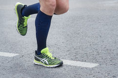 Feet of a running man. Running sport. Man runner legs and shoes in action on road outdoors Stock Images