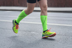 Feet Of A Running Man. Running sport. Man runner legs and shoes in action on road outdoors Royalty Free Stock Image