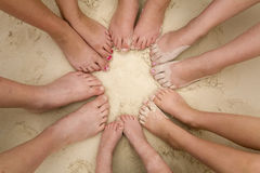Feet in sand. A bunch of kids feet laying in a circle in the sand Stock Photo