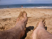 Feet in the sand. A pair of feet rests lazily on a wet, clumpy beach. People are frolicking in the water in the background royalty free stock photos