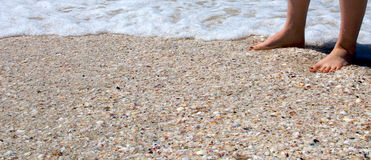 Feet in the Sand. A young woman's feet, with toenails painted a vibrant purple, at high tide Royalty Free Stock Photos