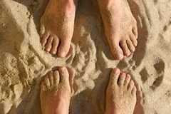 Feet in the sand. Two pairs of sandy feet Royalty Free Stock Image
