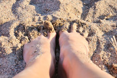 Feet in the sand. Top view Royalty Free Stock Image