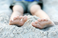 Feet in sand. Young boy's feet in white sand Royalty Free Stock Image
