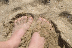Feet in sand Stock Photography