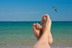 The feet in sand, against a sea landscape Royalty Free Stock Image