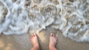 Feet in the sand on the beach Stock Photography