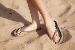 Feet in the sand with flipflops Stock Photos