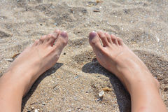 Feet in the sand. The summer came and so did the lovely trips to the beach. The capture represents the feet relaxing in the sand at the beach which is one of stock image