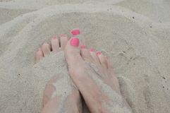 Feet in the sand. Women`s feet in the sand with pink nail polish royalty free stock photo