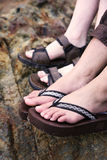 Feet in Sandals. A close up of a two pairs of feet wearing sandals - a girl and guy royalty free stock images