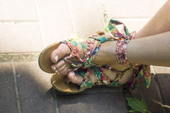Feet in sandals on fone tiles Stock Photo