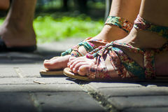 Feet in sandals on fone tiles Stock Image