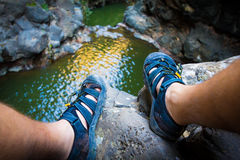 Feet sandals. Male sitting cliff. Man feet sandals. Cliff above lake Royalty Free Stock Photo