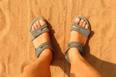 Feet in sandals on orange sand. Grey sandals, Feet in sandals,  orange sand, summer beach, sports wear, travelers feet, close up, Traveller legs, walking on the Stock Image