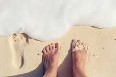Feet on the sandy beach with wave, vacation on ocean beach conce Royalty Free Stock Photos