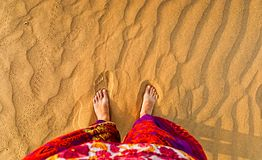 Feet in the sandy desert. Multi-colored clothes. View from above stock image