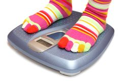 Feet on a scale. Feet in socks on a scale Royalty Free Stock Photography