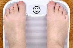 Feet on the scale. Barefoot person standing on the weight scale. The scale shows smiley face Royalty Free Stock Photography