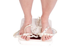 Feet on scales with tape Royalty Free Stock Photo