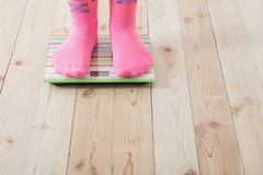 Feet on scales. On wooden floor Royalty Free Stock Images