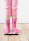 Feet on scales on wooden floor Royalty Free Stock Images